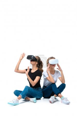 Photo for Young twins sitting and using virtual reality headsets on white - Royalty Free Image
