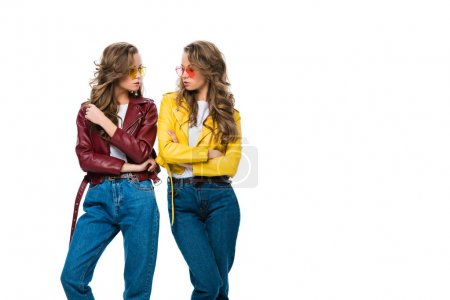 attractive stylish twins in leather jackets and sunglasses looking at each other isolated on white