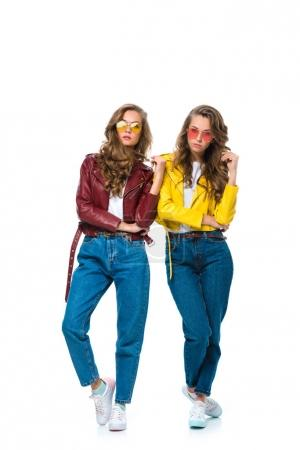 attractive stylish twins in leather jackets and sunglasses looking at camera isolated on white