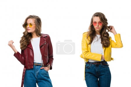attractive stylish twins in trendy leather jackets and sunglasses isolated on white