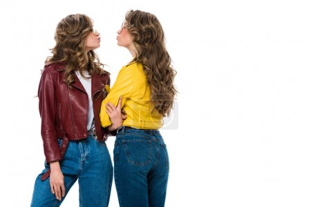 side view of attractive stylish twins in leather jackets and sunglasses going to kiss isolated on white