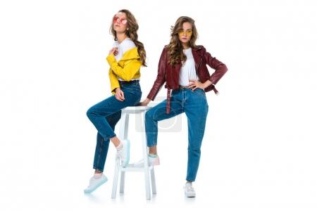 Photo for Attractive stylish twins in leather jackets and sunglasses with wooden chair isolated on white - Royalty Free Image
