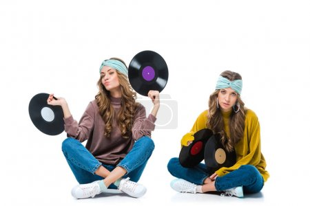 attractive retro styled young twins sitting with 12 inch vinyls isolated on white