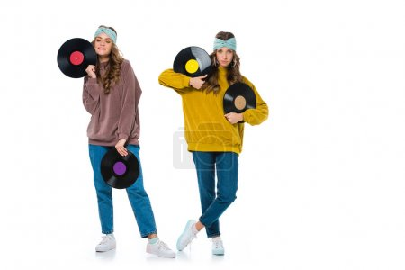 attractive retro styled young twins with phonograph records isolated on white