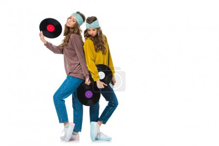 attractive retro styled young twins with LP vinyls isolated on white