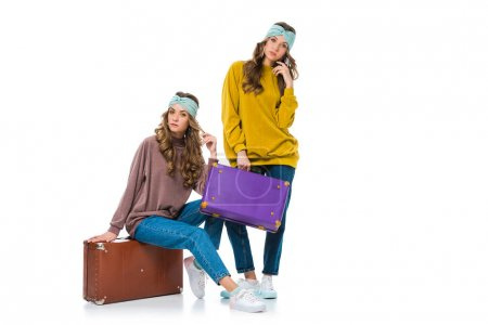 attractive retro styled twins with travel suitcases isolated on white