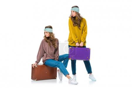 attractive retro styled twins with travel bags looking away isolated on white