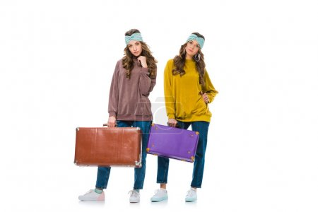 attractive retro styled twins standing with travel bags isolated on white