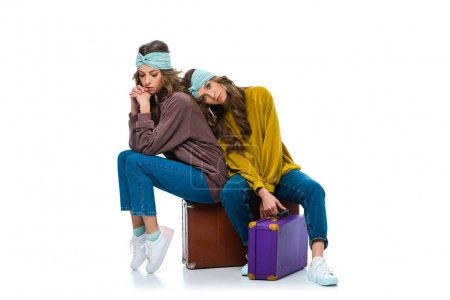 attractive retro styled twins sitting on travel bags isolated on white