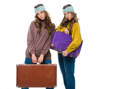attractive retro styled twins with travel bags looking at camera isolated on white