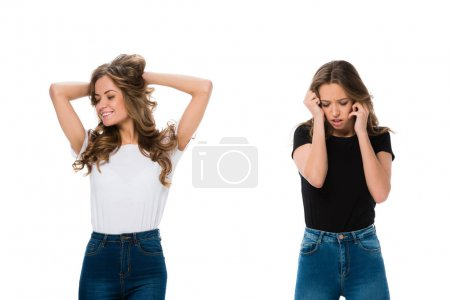 smiling and upset twins standing isolated on white