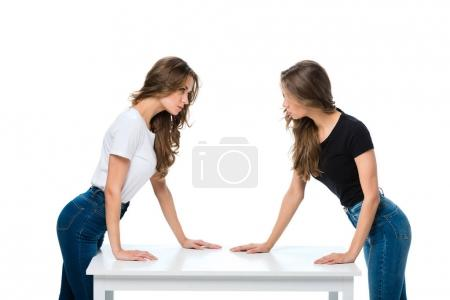 side view of angry twins looking at each other isolated on white