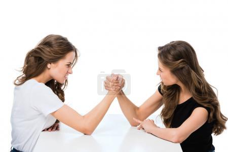 side view of angry twins armwrestling at table isolated on white