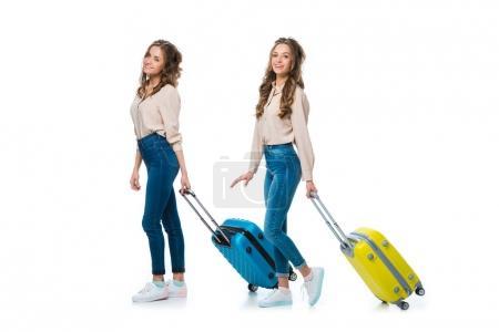 Foto de Vista lateral de los gemelos jóvenes felices con ruedas bolsos aislados en blanco, el concepto de viaje - Imagen libre de derechos