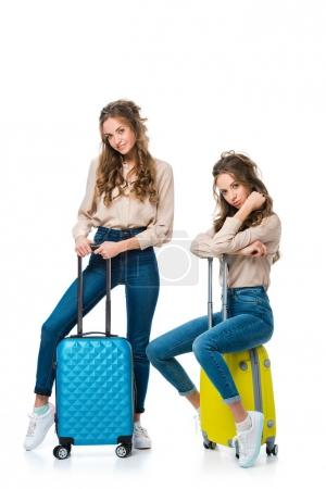 Photo for Attractive young twins with bags on wheels isolated on white, travel concept - Royalty Free Image