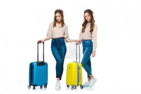 attractive young twins with suitcases isolated on white, travel concept