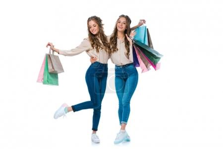 Photo for Smiling young twins hugging with shopping bags isolated on white - Royalty Free Image