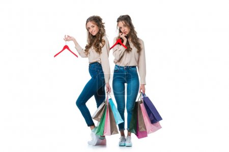 Photo for Attractive young twins with shopping bags and hangers isolated on white - Royalty Free Image