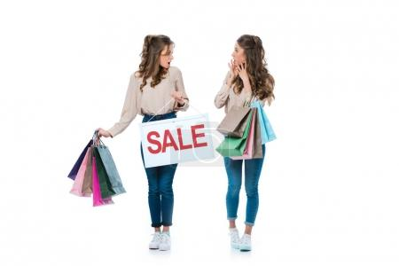 surprised young twins with sale sign and shopping bags isolated on white