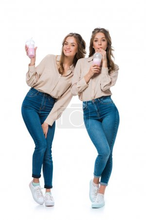 smiling attractive young twins drinking milkshakes isolated on white
