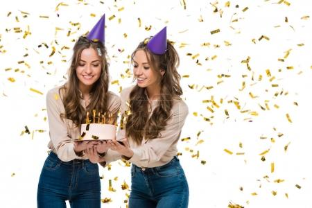 smiling twins in birthday caps looking at birthday cake under falling confetti isolated on white