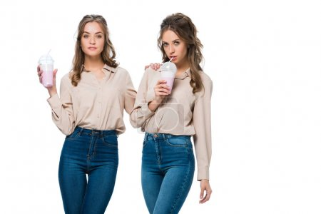attractive young twins drinking milkshakes isolated on white