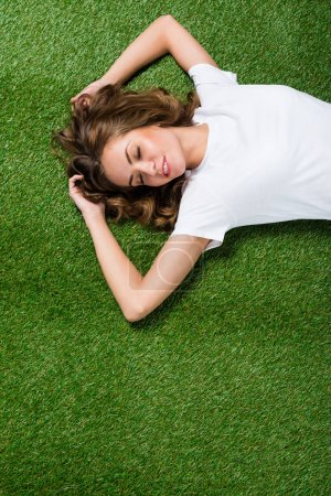 top view of attractive girl lying on green grass with closed eyes