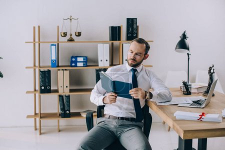 portrait of lawyer in eyeglasses reading book at workplace in office
