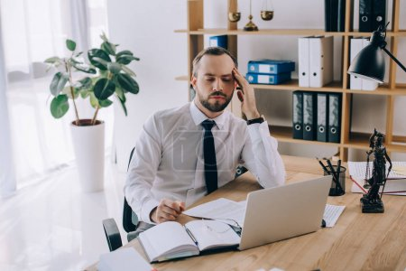 portrait of tired lawyer sitting at workplace with laptop and documents in office
