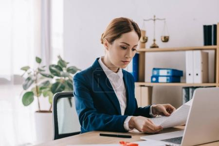 Photo for Side view of concentrated female lawyer working with documents at workplace in office - Royalty Free Image