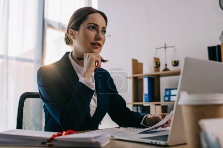Photo pour Avocate à lunettes au lieu de travail avec des documents et ordinateur portable au bureau - image libre de droit