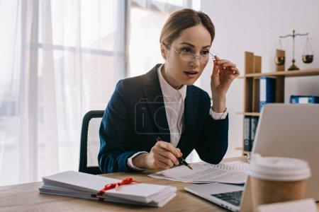 Photo pour Vue latérale de avocate faisant de la paperasserie sur le lieu de travail avec ordinateur portable au bureau - image libre de droit