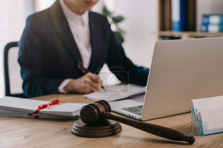 Photo for Cropped shot of female lawyer doing paperwork at workplace with laptop and gavel in office - Royalty Free Image