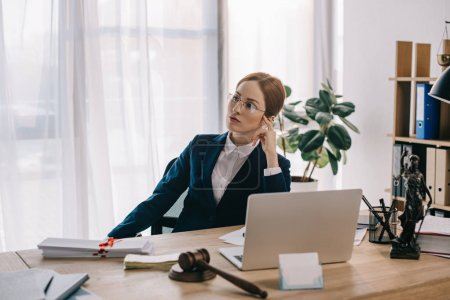 portrait of pensive female lawyer at workplace with gavel and laptop in office