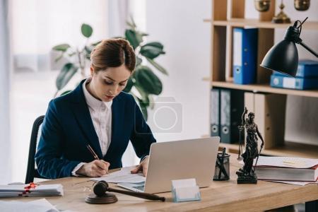 Photo pour Avocate en costume au milieu de travail avec ordinateur portable, marteau et femida au bureau - image libre de droit