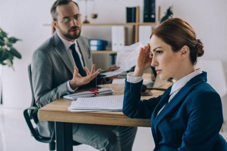 selective focus of lawyers discussing contract during meeting in office