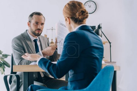 partial view of lawyers discussing contract during meeting in office