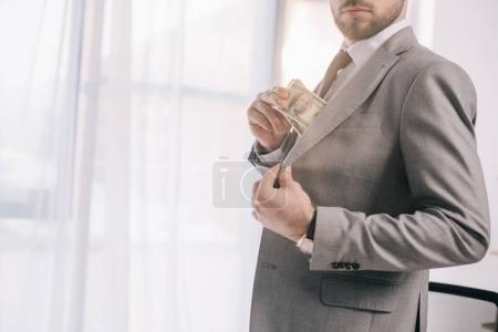 cropped shot of businessman in suit putting dollar banknotes into pocket in office