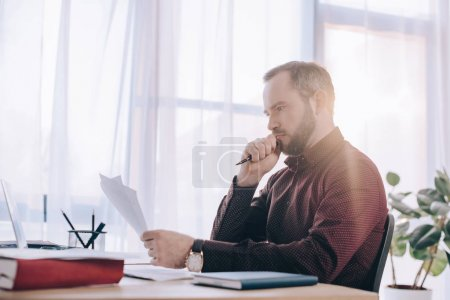 side view of concentrated businessman doing paperwork at workplace in office