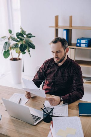 Photo pour Portrait d'homme d'affaires, faire de la paperasse sur lieu de travail avec ordinateur portable au bureau - image libre de droit