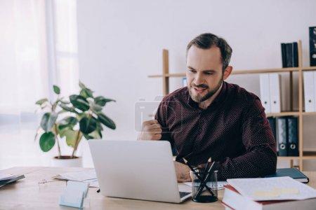 Photo pour Portrait d'homme d'affaires, écran d'ordinateur portable au lieu de travail au bureau en regardant - image libre de droit