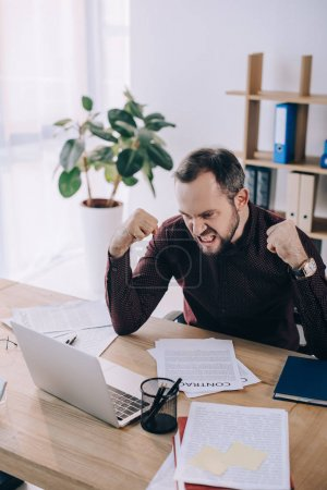 Photo for Angry and overworked businessman at workplace with laptop in office - Royalty Free Image