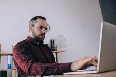 Photo for Focused businessman working on laptop at workplace in office - Royalty Free Image