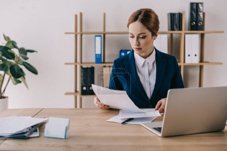 Photo for Focused businesswoman in suit doing paperwork at workplace in office - Royalty Free Image