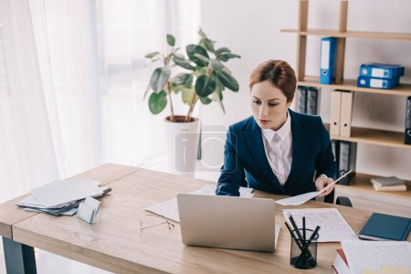 portrait of businesswoman in suit working on laptop at workplace in office