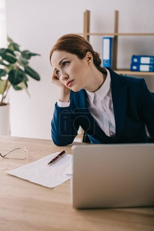 portrait of tired businesswoman looking away at workplace with laptop in office
