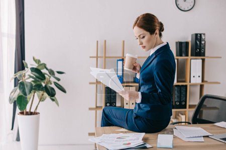 side view of focused businesswoman with papers and coffee to go sitting on table in office