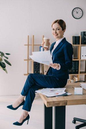 Photo pour Vue latérale d'une femme souriante avec papiers et café pour aller assis sur la table au bureau - image libre de droit