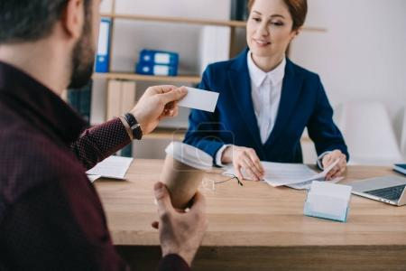 partial view of client with blank card and businesswoman at workplace in office