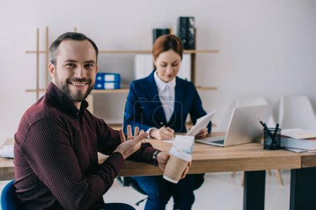 selective focus of smiling client with coffee to go pointing at businesswoman at workplace in office